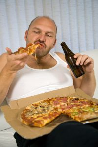 Unattractive overweight man eating a big slice of pizza and drinking beer